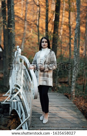 Fashion autumn portrait of stylish model woman, posing. Woman posing in park in warm coat, autumn fashion trend. Beautiful young teen girl  #1635658027