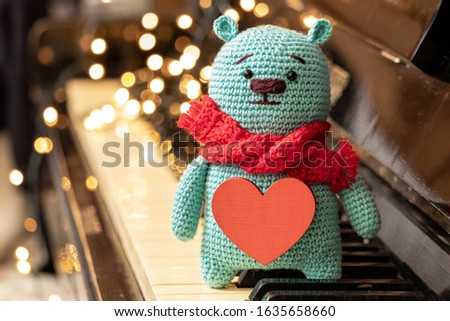 Teddy bear with a heart. Valentine's day celebration. Lights in the background. Cute soft toy in a red knitted scarf on the piano keys. #1635658660