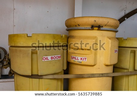 Two bright yellow plastic bins, labeled with oil Boom and Spill kit secured on the deck of a canadian ferry boat. Looking old and dirty.