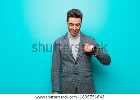 young arabian man smiling cheerfully and casually, looking downwards and pointing to chest against blue wall #1635751843
