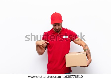 smiling cheerfully and casually, looking downwards and pointing to chest. delivery concept #1635778510