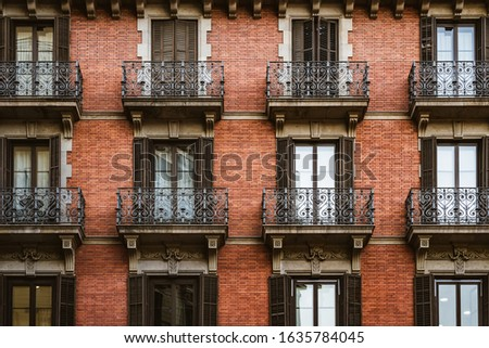 Red brick facade with wrought iron balconies