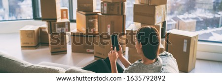 Moving boxes woman using phone panoramic for move to college leaving apartment ready for movers pick-up with packages of cardboard box for new home move in. Banner. #1635792892