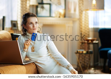 pensive elegant 40 years old housewife in white sweater and skirt with credit card making online purchases on e-commerce website in the modern house in sunny winter day. #1635905170