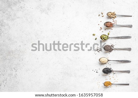 Various Seeds on white background. Assortment, set of  sesame seeds, flax seed, sunflower seeds, pumpkin seed, chia, hemp seeds in spoons, healthy food ingredients, top view, copy space. #1635957058