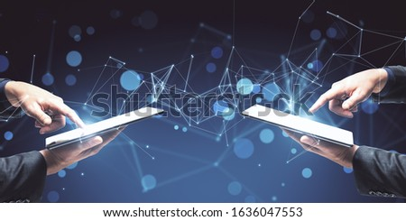 Two businessman using tablets on abstract glowing blue polygonal wallpaper. Mock up.