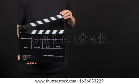 Female model is holding clapperboard or movie slate in studio shooting .It is use in video production and cinema industry on black background.
