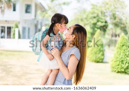 Coronavirus, Education New normal concept.Little chinese girl and chinese mother holding her kid wearing mask for protect pm2.5 in the garden at home.Covid19 coronavirus Kawasaki disease in children. #1636062409