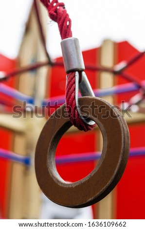 Colorful playground for children. Gymnastic ring on the playground outdoors. Close Up of a wooden gymnastic ring on a red rope. Selective focus. The vertical location of the picture.