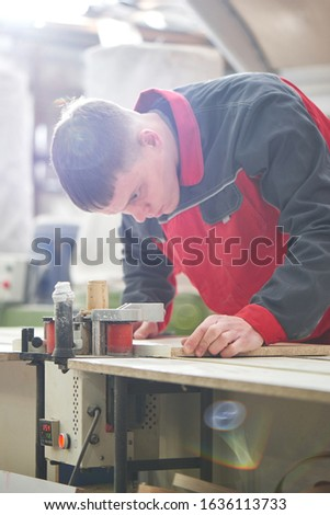Process of production and manufacture of wooden furniture in furniture factory. Worker carpenter man in overalls processes wood on special equipment #1636113733