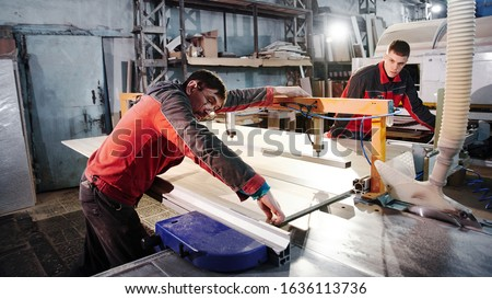 Process of production and manufacture of wooden furniture in furniture factory. Worker carpenter man in overalls processes wood on special equipment #1636113736