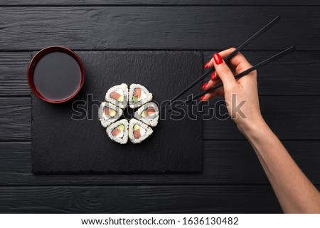 Woman holds sushi with chopsticks. Young woman holding sushi with a chopsticks, isolated on black. Sushi Roll with a woman hand holding chopsticks. #1636130482