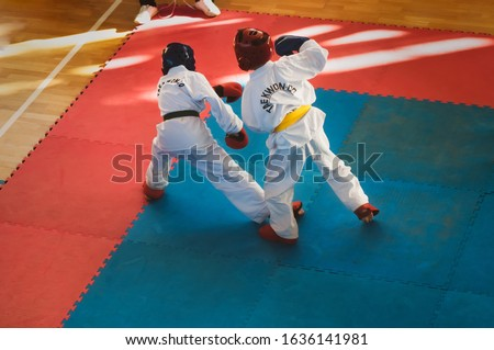 Taekwondo.  Kids in traditional kimano, hard hats and gloves. Sports duel. For atmospheric, a motion blur film noise effect has been added. Text on jacket: Taekwondo is the name for martial art. #1636141981