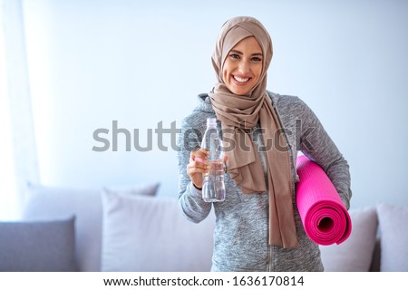 Fit young muslim woman drinking water . Young muslim woman ready to running. Young muslim woman holding bottle of water and fitnes mate. Portrait of muslim woman likes her active life. #1636170814