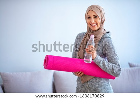 Fit young muslim woman drinking water . Young muslim woman ready to running. Young muslim woman holding bottle of water and fitnes mate. Portrait of muslim woman likes her active life. #1636170829