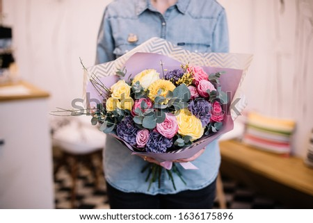 Very nice young woman holding big and beautiful bouquet of fresh roses, carnations, genista, eucalyptus, flowers in yellow, pink and purple colors, cropped photo, bouquet close up #1636175896
