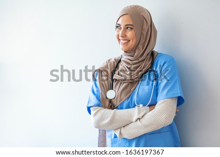 Arab nurse woman wearing hijab over isolated background looking away to side with smile on face, natural expression. Laughing confident. Authentic Confident Middle Eastern Healthcare Worker #1636197367