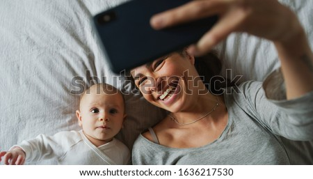 Authentic close up of neo mother and her newborn baby making a selfie or video call to father or relatives in a bed. Concept of technology, new generation,family, connection, parenthood, authenticity #1636217530