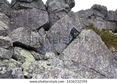 Southern Urals. A mature tourist makes an ascent to the top along a large stone placer. #1636232596