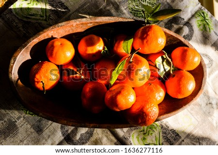 a wooden fruit bown full of clementines clementine (aka Citrus × clementina or easy peeler in British English), a citrus fruit hybrid between a willowleaf mandarin orange and a sweet orange.  #1636277116