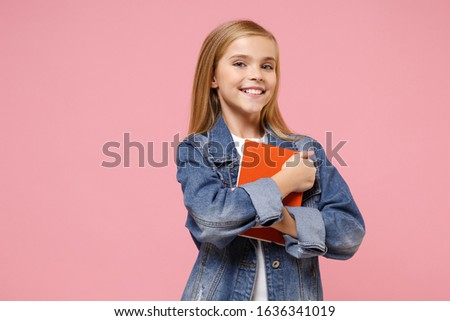 Smiling little blonde kid girl 12-13 years old in denim jacket isolated on pastel pink background children studio portrait. Childhood lifestyle concept. Mock up copy space. Holding book, notebook Royalty-Free Stock Photo #1636341019
