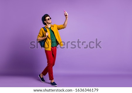 Full body profile side photo of positive guy tourist blogger go walk make selfie using smartphone wear modern casual style clothing over purple color background