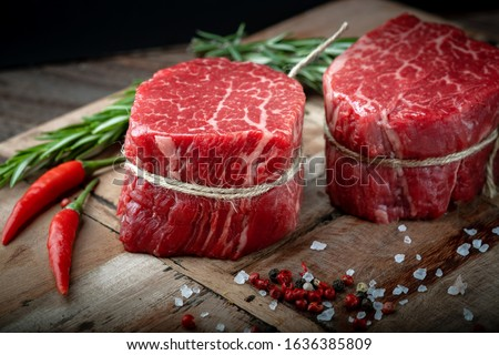 Raw beef filet Mignon steak on a wooden Board with pepper and salt, black Angus marbled meat #1636385809