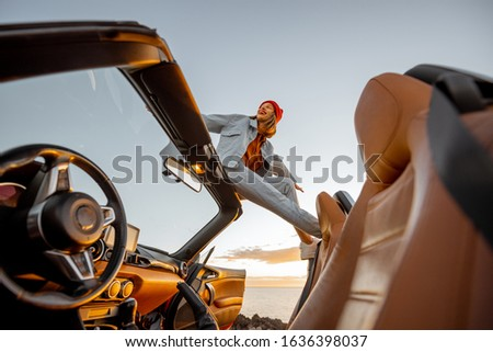 Woman enjoying beautiful view on the ocean, sitting on the car roof top during a sunset. Nature enjoyment and carefree travel by car concept #1636398037