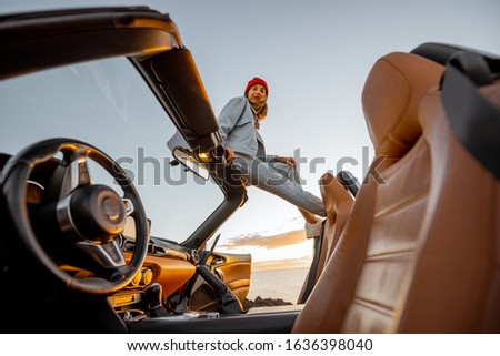 Woman enjoying beautiful view on the ocean, sitting on the car roof top during a sunset. Nature enjoyment and carefree travel by car concept #1636398040