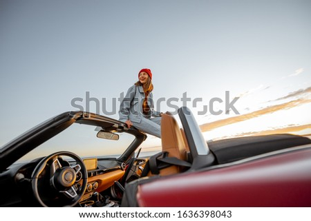 Woman enjoying beautiful view on the ocean, sitting on the car roof top during a sunset. Nature enjoyment and carefree travel by car concept #1636398043