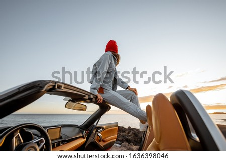 Woman enjoying beautiful view on the ocean, sitting on the car roof top during a sunset. Nature enjoyment and carefree travel by car concept #1636398046