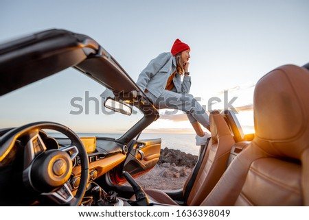 Woman enjoying beautiful view on the ocean, sitting on the car roof top during a sunset. Nature enjoyment and carefree travel by car concept #1636398049