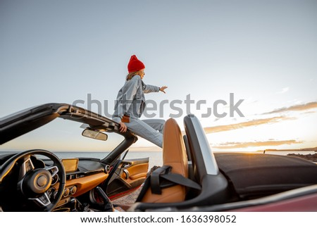 Woman enjoying beautiful view on the ocean, sitting on the car roof top during a sunset. Nature enjoyment and carefree travel by car concept #1636398052