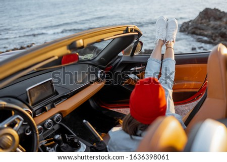 Woman enjoying beautiful sunset view on the ocean, pulling legs out of the car. Carefree travel and nature enjoyment concept #1636398061