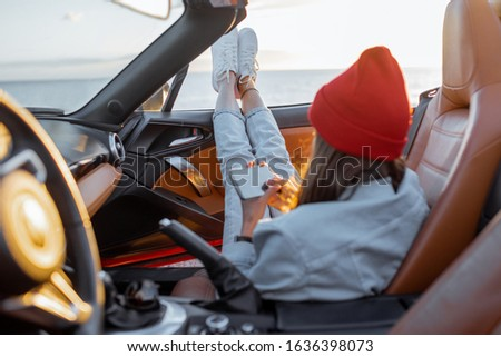 Woman enjoying beautiful sunset view on the ocean, pulling legs out of the car. Carefree travel and nature enjoyment concept #1636398073