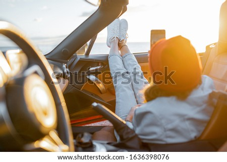 Woman enjoying beautiful sunset view on the ocean, pulling legs out of the car. Carefree travel and nature enjoyment concept #1636398076