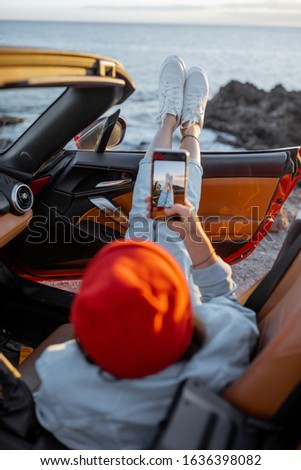 Woman enjoying beautiful sunset view on the ocean, pulling legs out of the car. Carefree travel and nature enjoyment concept #1636398082