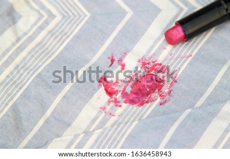 Pink lipstick stain on cloth fabric from accident. dirty stains in daily life for cleaning concept  #1636458943