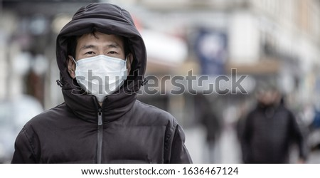 The image face of a young Asian man wearing a mask to prevent germs, toxic fumes, and dust. Prevention of bacterial infection Corona virus or Covid 19 in the air around the streets and gardens. #1636467124