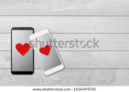 on white wooden background isolated two smartphones with hearts on the screen, modern gadget love and relationship, love messages, Valentine day concept #1636494505