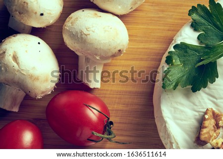 Cheese mushrooms and tomatoes on wooden deck. Royalty-Free Stock Photo #1636511614