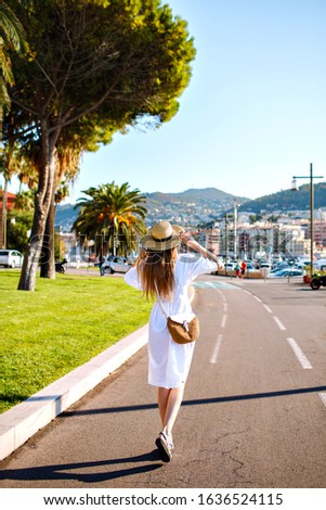 Outdoor travel picture of stylish young woman wearing elegant dress hat and straw back walking alone at amazing France small city, enjoying her trip, summertime vacations.