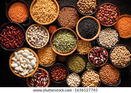 Legumes, a set consisting of different types of beans, lentils and peas on a black background, top view. The concept of healthy and nutritious food #1636527745