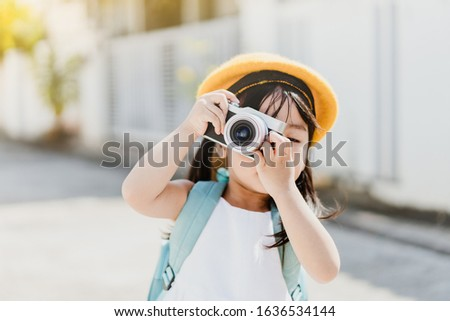 Cute little asian girl takes picture with camera for mom.Traveller cheerful toddler girl holding mirrorless camera.Vacation Travel lifestyle, Education and Smart kid girl concept.