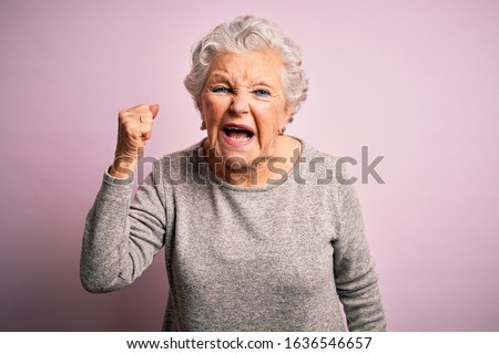 Senior beautiful woman wearing casual t-shirt standing over isolated pink background angry and mad raising fist frustrated and furious while shouting with anger. Rage and aggressive concept. Royalty-Free Stock Photo #1636546657