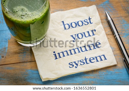 boost your immune system - inspirational handwriting on a napkin with a glass of fresh, green, vegetable juice, healthy lifestyle and wellbeing concept #1636552801