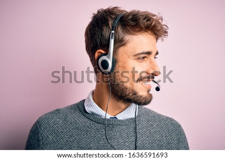 Young call center agent man with beard wearing headset over isolated pink background looking away to side with smile on face, natural expression. Laughing confident.