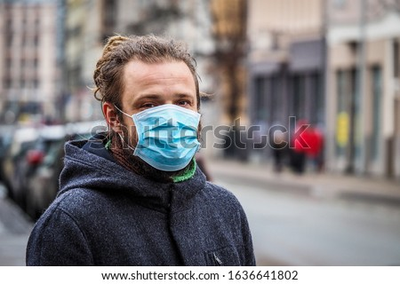 Handsome young European man in winter clothes on the street with a medical face mask on. Closeup of a 35-year-old male in a respirator to protect against infection with influenza virus or coronavirus #1636641802