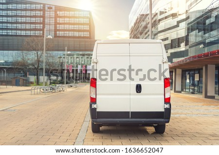 Small cargo delivery van driving in european city central district. Medium lorry minivan courier vehicle deliver package at residential office building in downtown area. Commercial shipping logistics. #1636652047