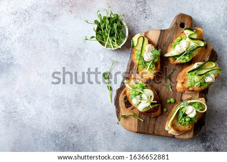 Appetizer crostini with mashed green pea, mozzarella, pea sprouts and zucchini ribbons on wooden board. Delicious healthy snack, spring appetizers #1636652881